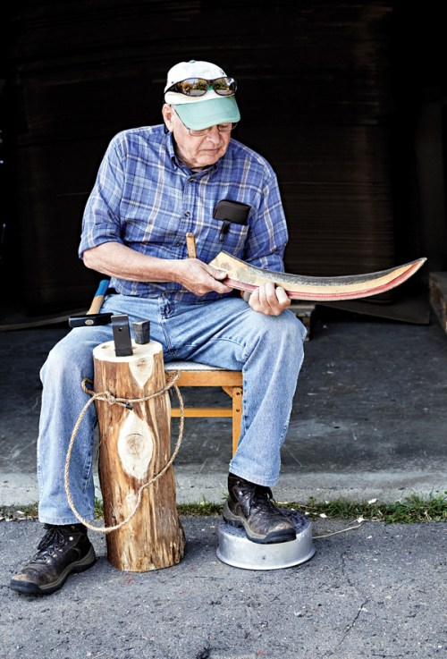 Richard Scott uses a hammer and anvil to sharpen a scythe blade.